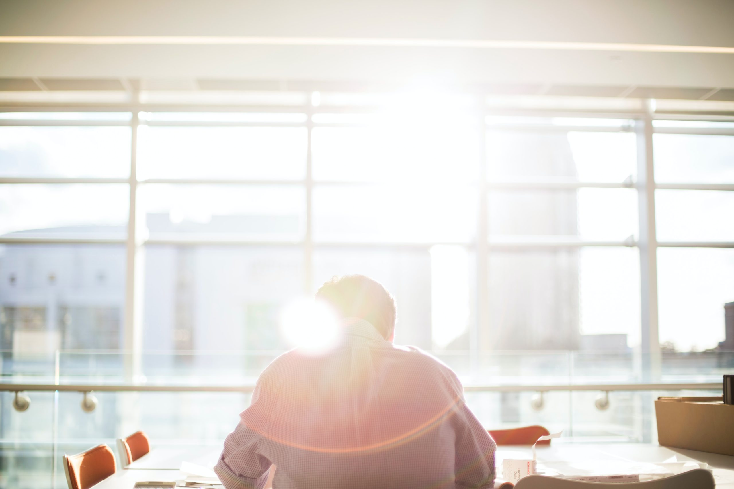 A picture of a man working in an office next to a window with the sun shining through